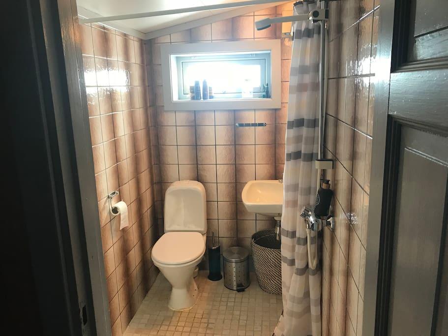 Lite bad med toalett og dusj. Varmekabler i gulv.