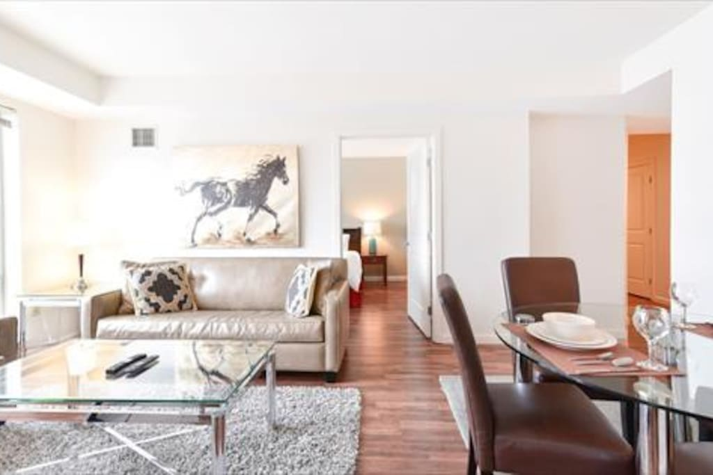 Comfortable living room with pullout sofa bed, club chair and over-sized windows providing lovely natural light
