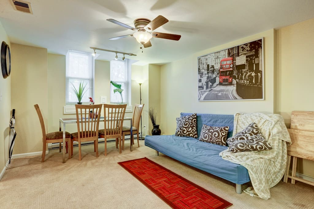 Open and brightly lit living/dining room with ceiling fan