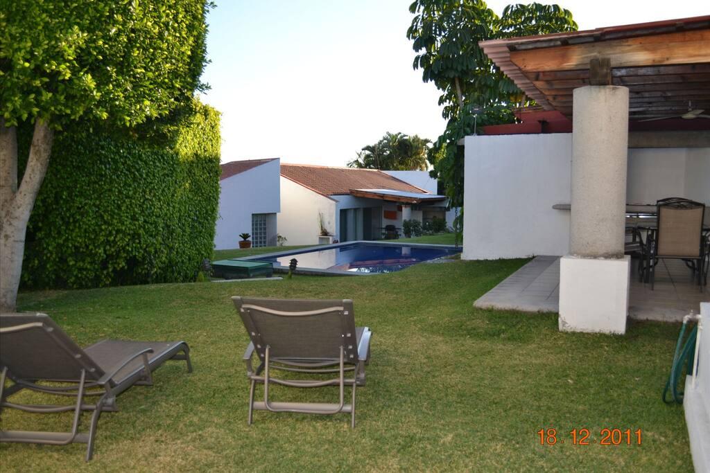 Terraza con asador y pequeño espacio de jardin con alberca compartida con 6 casitas