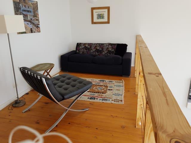 Sala de estar en segundo piso con sofá cama matrimonial