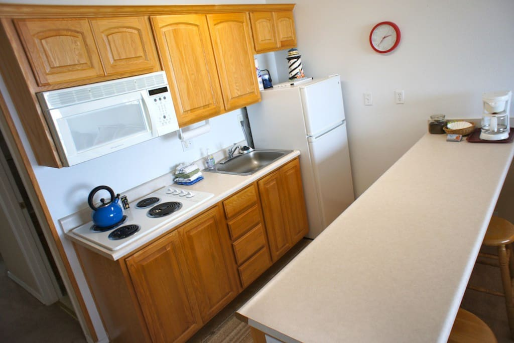 Kitchenette with a stovetop, fridge, microwave, coffee pot and basic cookware.