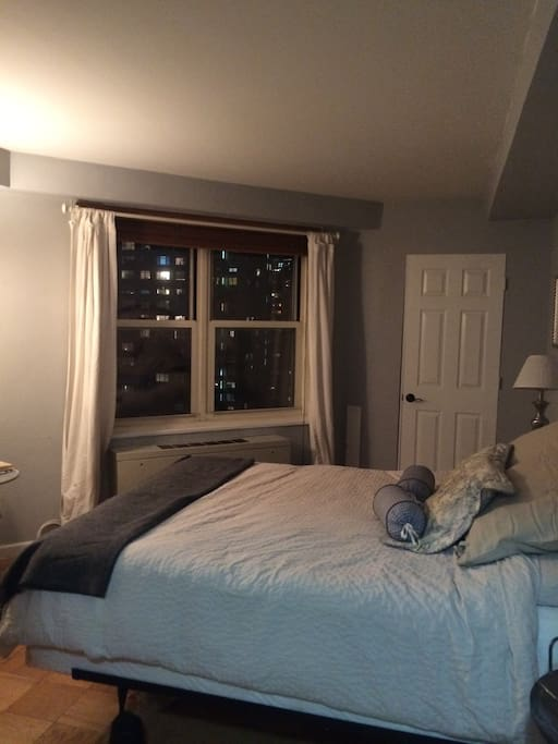 Master bedroom has large window that looks out onto the new york skyline