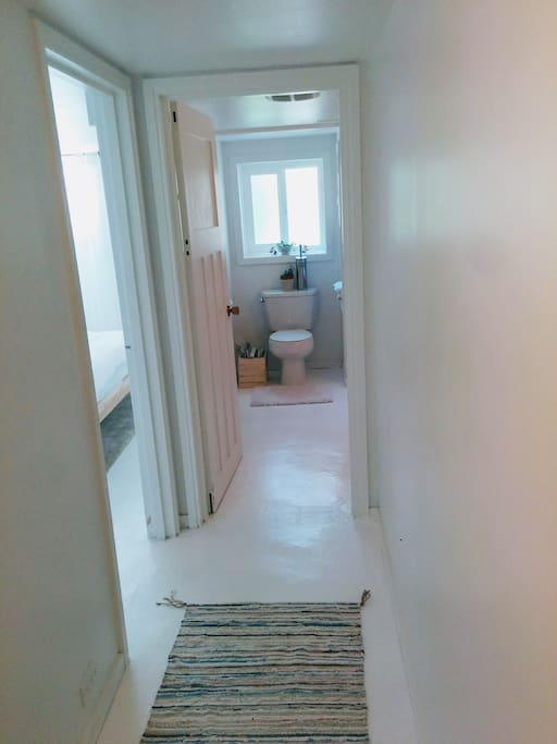 Hallway to bathroom with shower only.