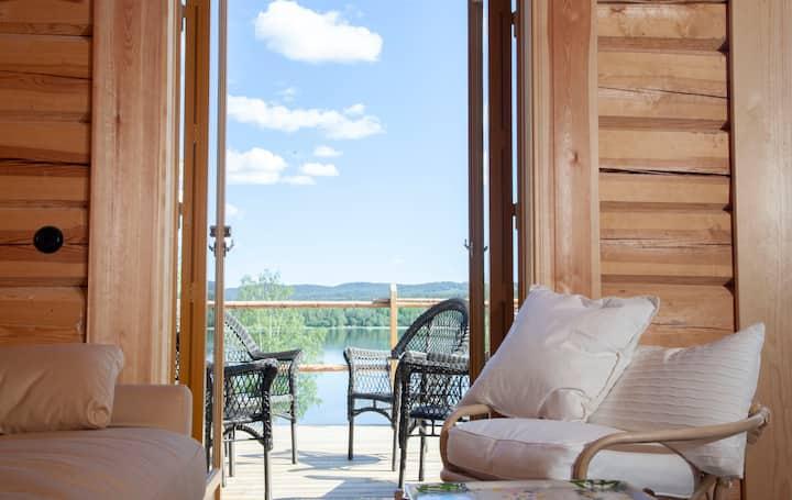 Stor altan med utsikt över sjö och vacker natur.