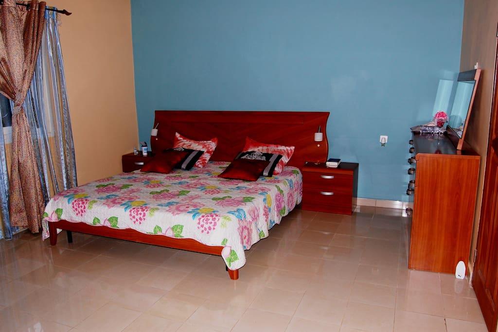 Grand lit deux places douillet, matelas orthopédique, lampes de chevet, commode avec miroir, penderie, avec salle de bain équipée et eau chaude