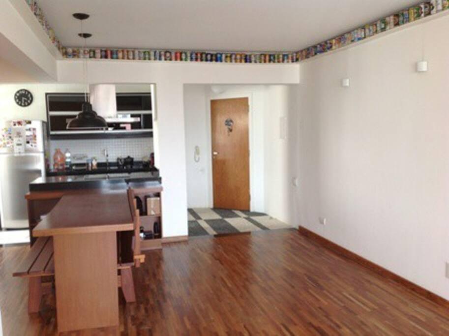 mesa de jantar à esquerda, hall de entrada ao fundo/direita.