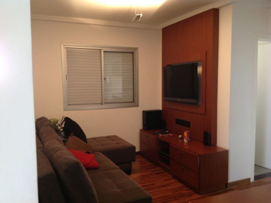 home theater com sofá retrátil, TV e bancada.