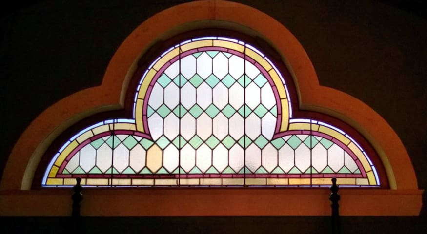 Original stained glass window in loft. Faces east--the morning sun shining through it is simply stunning.