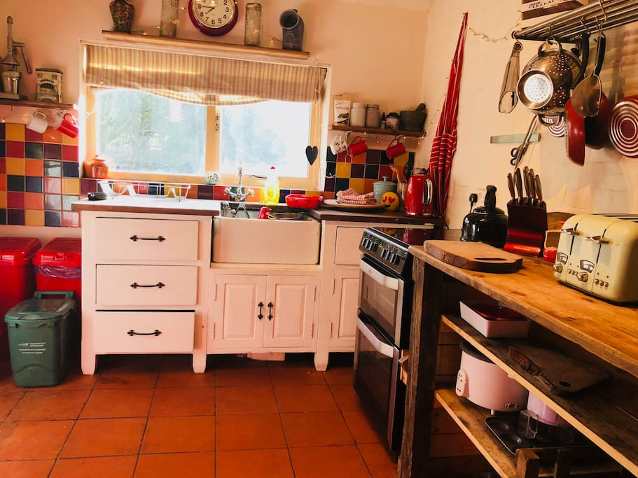 The country kitchen is colourful quirky and inviting with it's custom built rustic waney edge worktop and natural wood chopping boards...Complete with full size electric cooker and smeg fridge...And bursting with character!