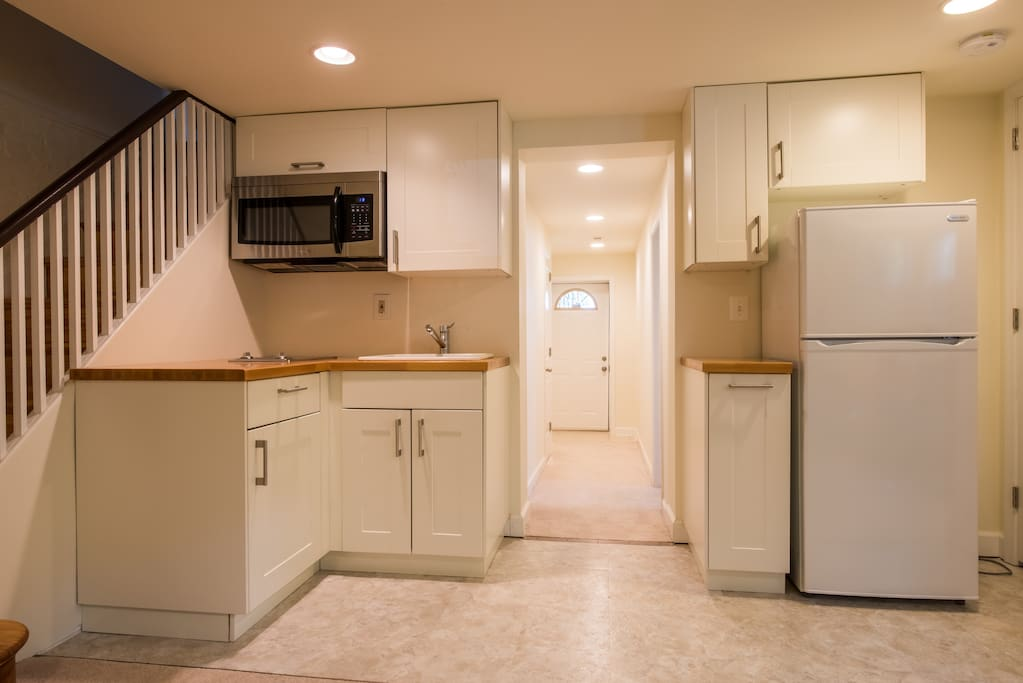 Kitchen with two-burner stove, full-size refrigerator and microwave.