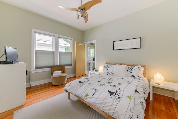Master bedroom with queen size bed, en-suite half bath, closet, chest of drawers, and smart TV with cable.
