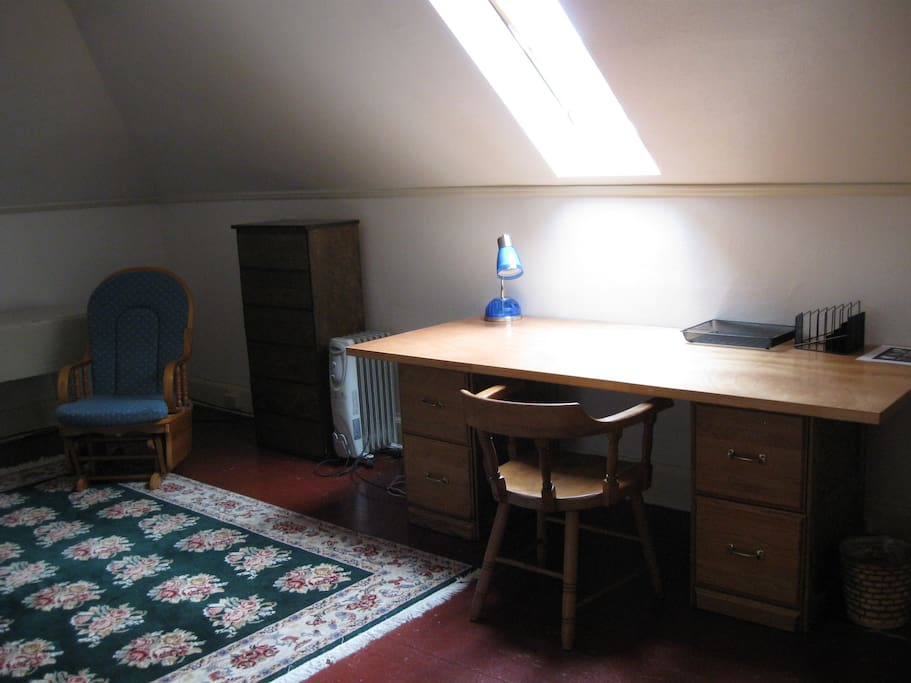 Large bedroom study with double bed and desk.