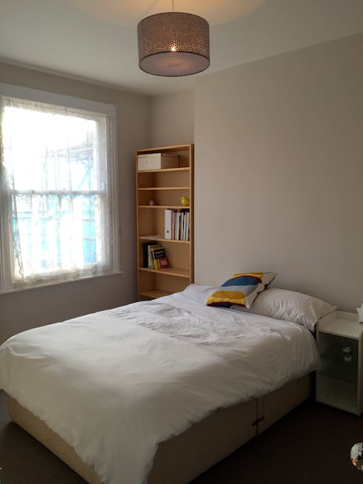 Light, bright, newly decorated double bedroom with bookshelf