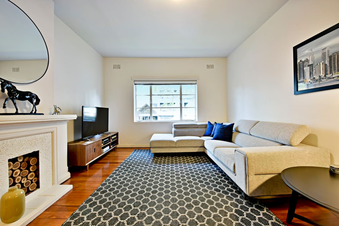 Main lounge room, with corner suite, digital TV, decorative fire place, rug, floor rug and window.