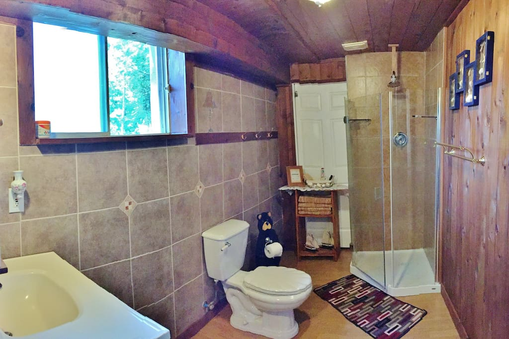 Newly renovated large 3 pc bathroom with corner shower and fresh towels provided.