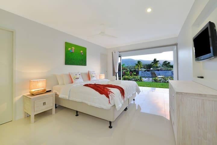 Master bedroom with en-suite, walk-in wardrobe, TV and pool view.