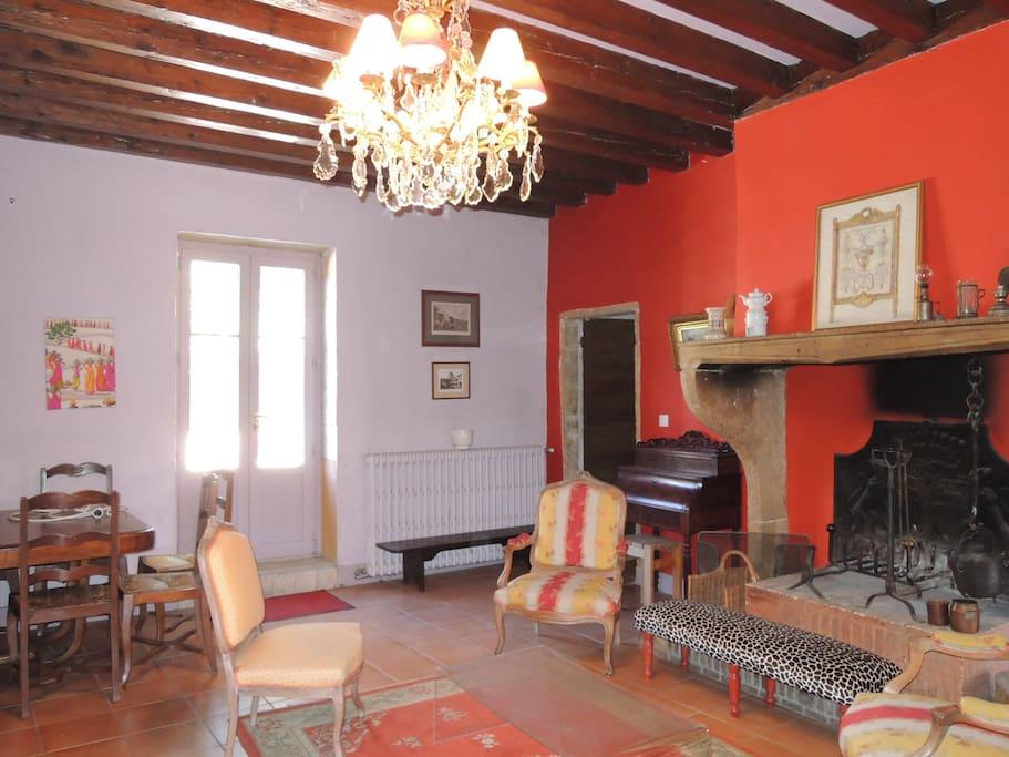 séjour ancien donnant sur jardin cheminée, fauteuil, table de salle à manger et chaises