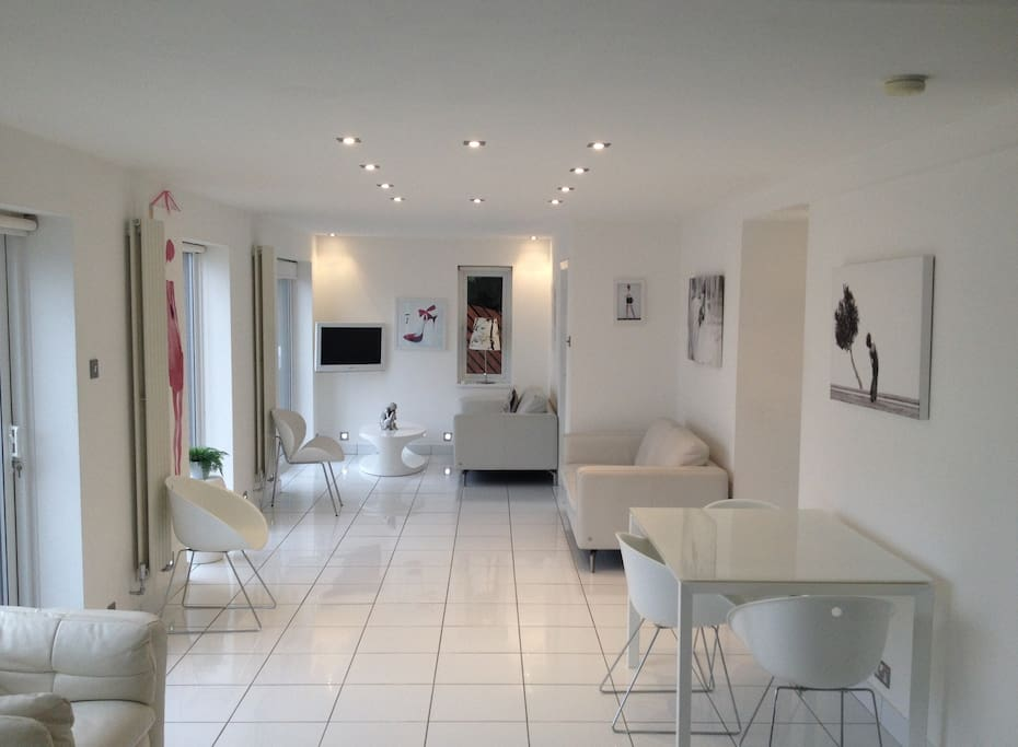 Rear facing white ceramic tiled modern living area with garden views through large patio windows and doors.