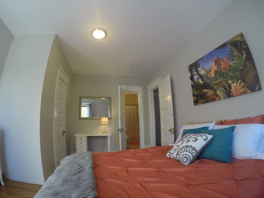 A large suite with queen bed, desk, lots of sunlight, and an attached private bathroom.