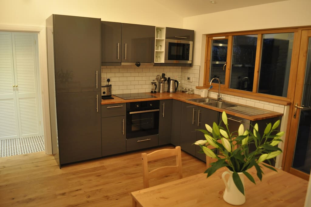 Modern dining kitchen complete with built in oven, microwave, dishwasher, fridge & freezer and a variety of utensils.