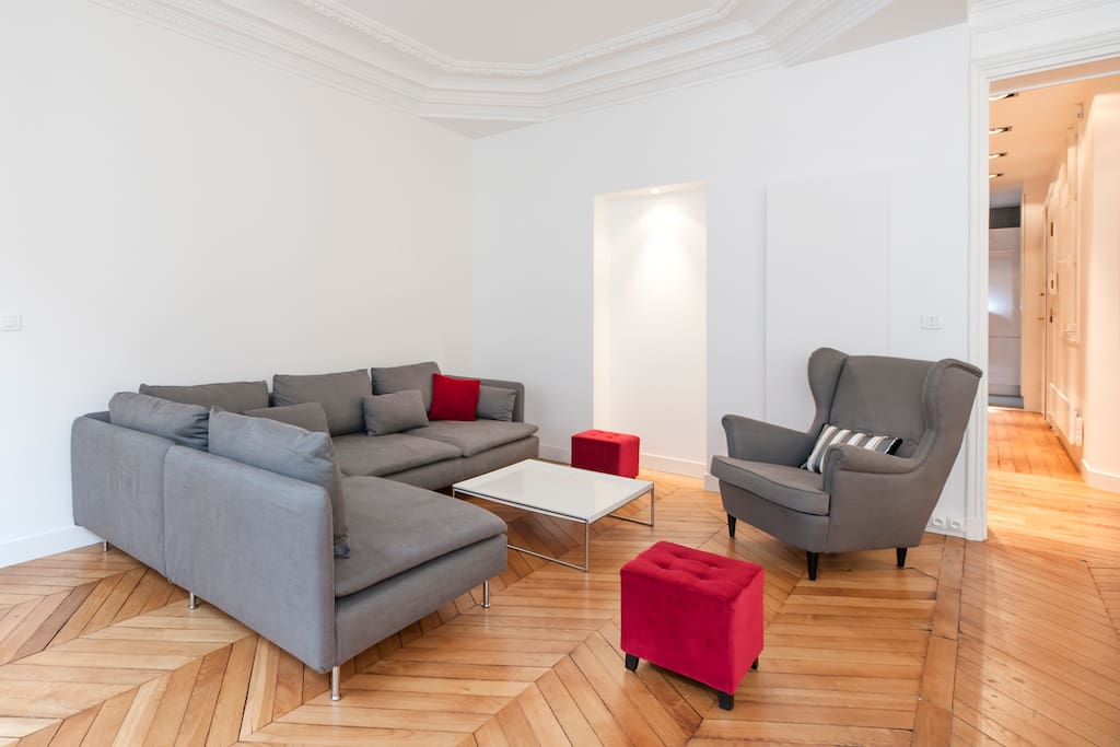 Spacious and stylish double living-room with a designer couch, a coffee table, an armchair and two velvet stools.