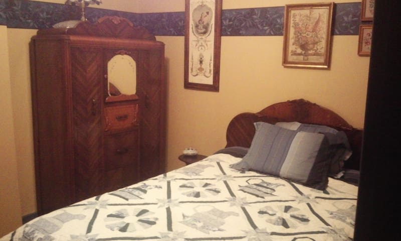 Stately blue accents in this full bedroom, closet, antique furniture. Antique quilt.