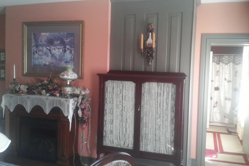 View of fireplace, antique cabinet with flatscreen TV behind, movies, bath off living room and off bedroom.
