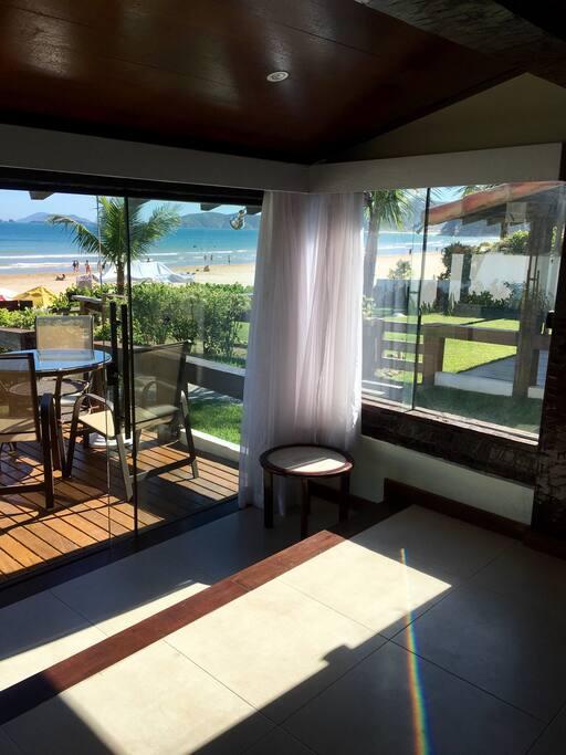 Sala ampla com vista frontal e lateral do mar. Piso em porcelanato e portas e janelas em blindex .