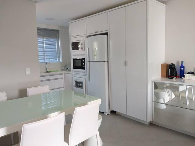 Visão da cozinha e espaço de refeição.