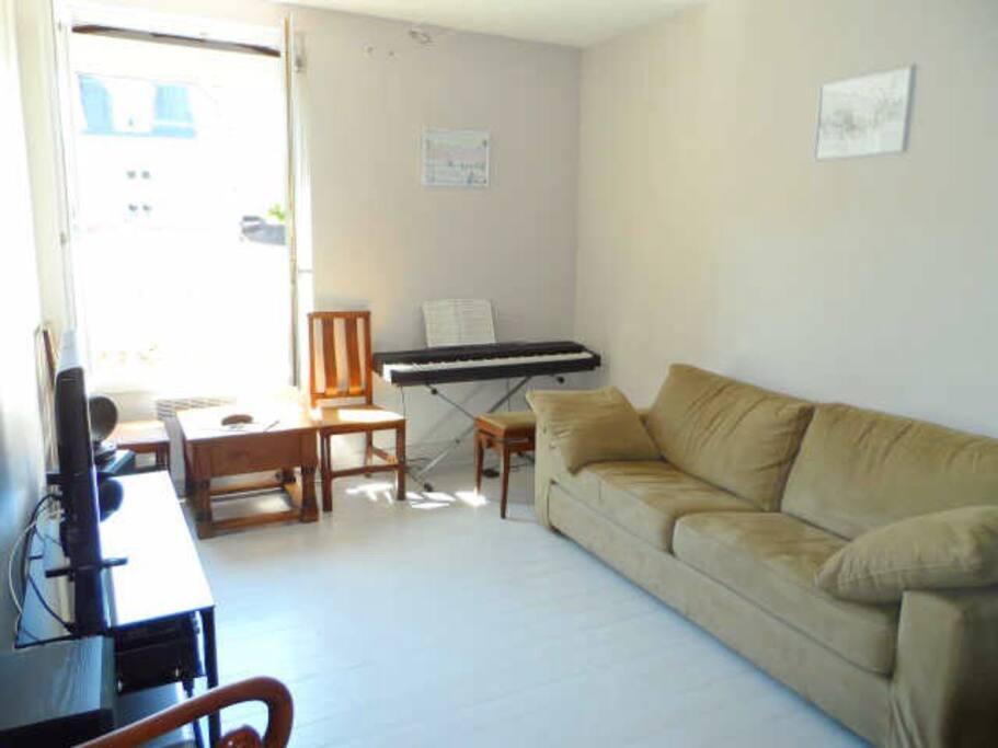 séjour avec canapé lit , tv/hifi, piano