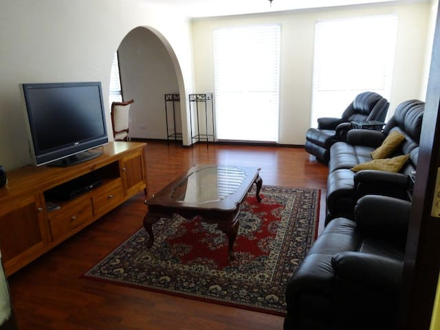 Spacious well appointed lounge room furnished with a 5-seater leather lounge suite, coffee table, TV and DVD player.