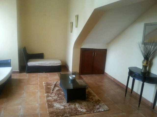 Comfortable furnished foyer at the entrance to the apartment, with separate seating area from the living room.