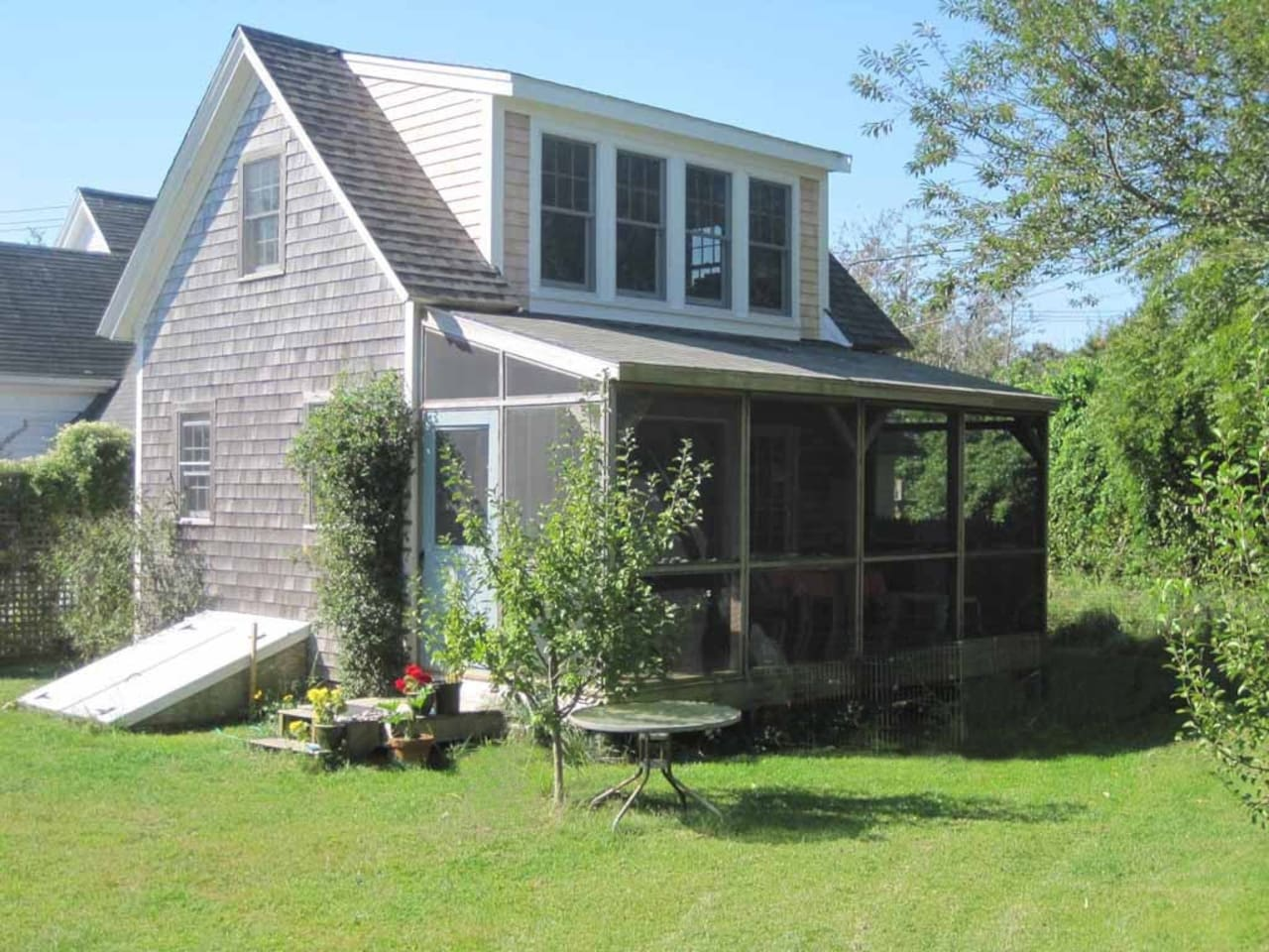 View of the  cottage from back yard showing screen porch and upstairs bedroom with dormer windows.