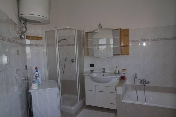 Bagno con doccia e vasca, dotato di lavatrice