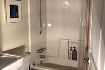 Full bath with multi-function shower head and hand-shower, fully equipped with all bath essentials