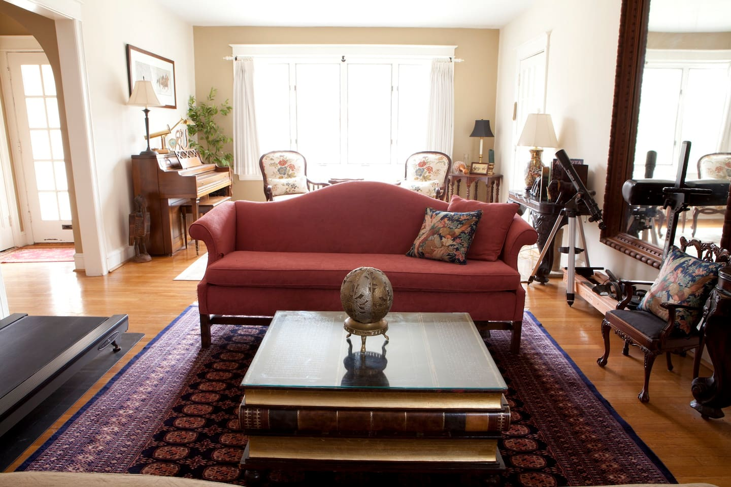 Living room (treadmill is no longer there); front door & entryway on the left, fireplace is behind the photographer.