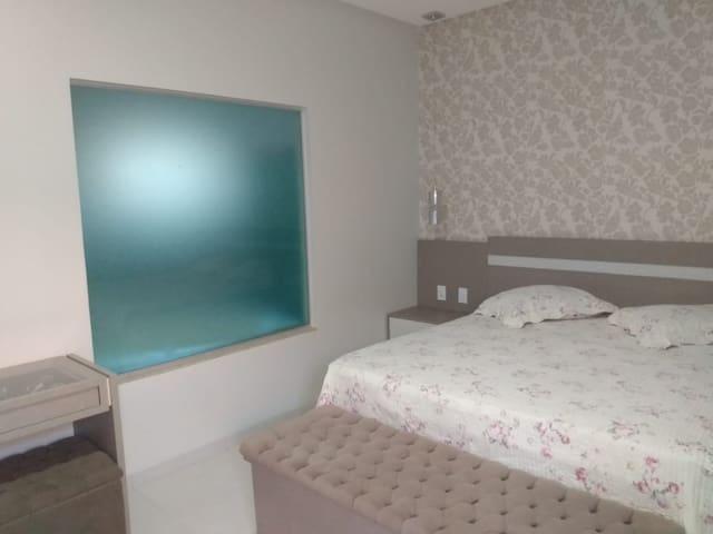 Suite Master, com cama de casal queen, frigobar, climatizador, ventilador e escrivaninha.