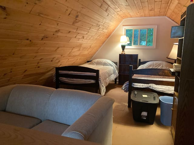 Twin beds and love seat in loft.