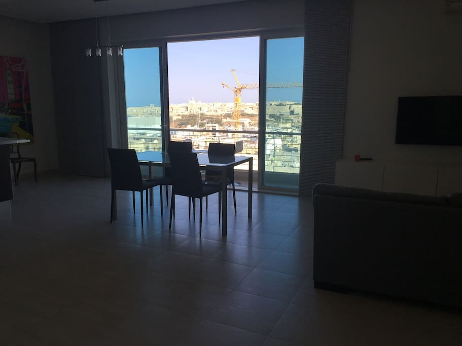 Spacious living dining kitchen area with big terrace doors, balcony and spectacular views on the capital Valletta, 180 degrees over the island and lots of morning light (South facing).