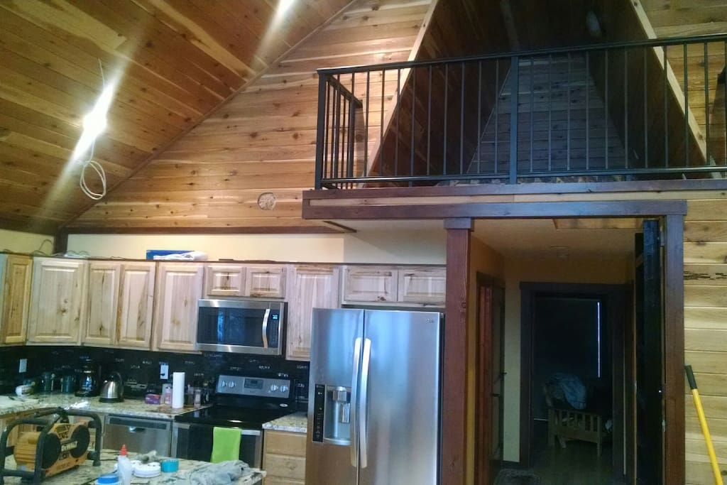 Loft above accessed by custom steel ladder overlooks the great room and sleeps 2 comfortably in a king size bed.