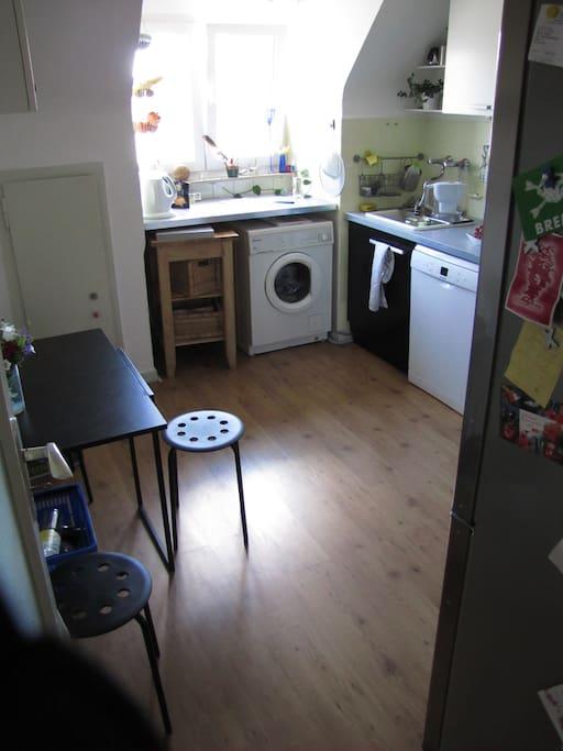 Küche mit Waschmaschine und kleinem Frühstückstisch