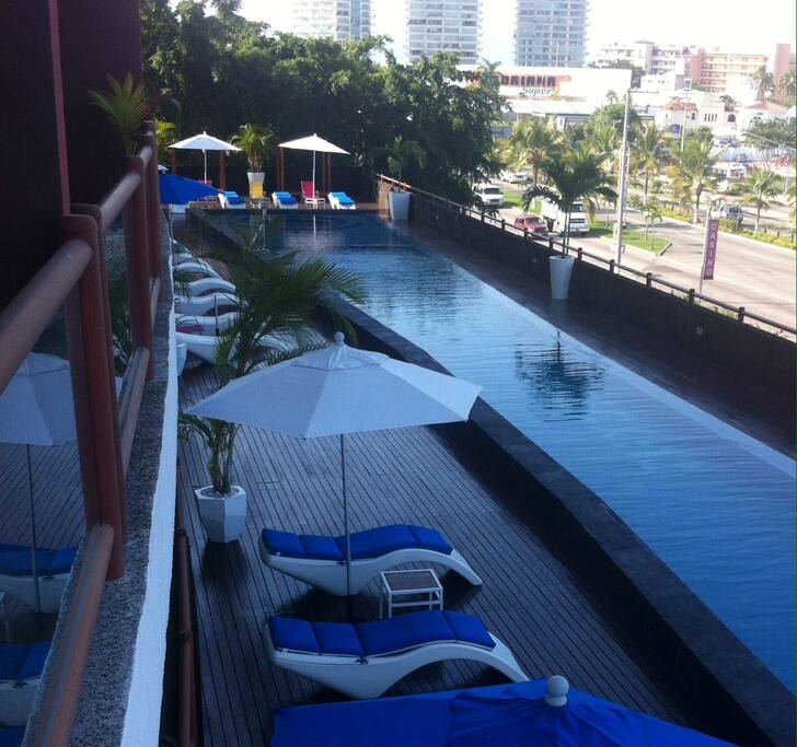 Large swimming pool, umbrellas & lounge chairs at the deck