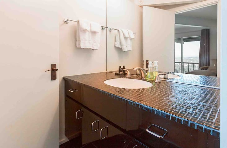 """Guest bathroom complete with soap, shampoo, hair dryer, bath sheets, and large 50"""" countertop to spread ones toiletries upon."""