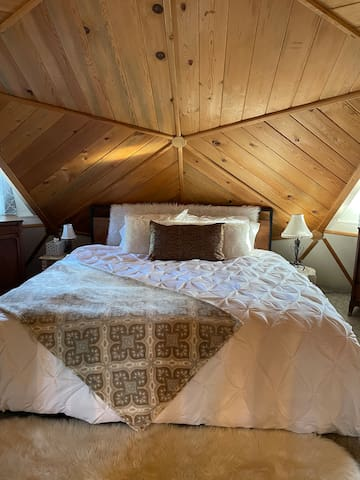 Loft bedroom with very comfortable king mattress. Best place to sleep in the house for sure. Really magical to wake up here (full disclosure: not the most private when it's a full house)