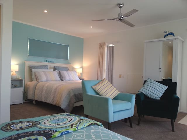 A complete suite with King size bed nook, separate King single bed, wardrobe and comfortable arm chairs. Dining and food prep area, and private internal bathroom ensuite.