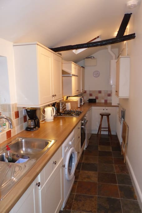 Galley kitchen with washing machine and dishwasher.