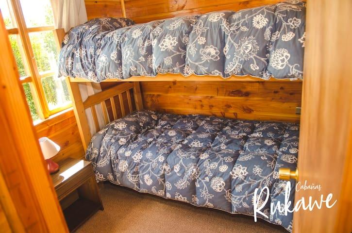 Litera con dos camas individuales, closet, percheros, velador  y lámpara de velador. Las camas incluyen frazadas, sábanas, almohada  y cubrecama
