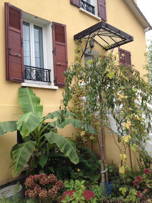 Un autre angle de la maison avec le bananier au premier plan.