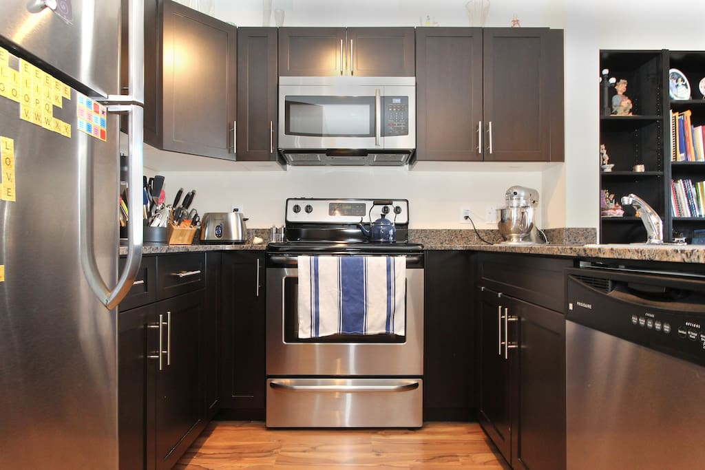 Four piece modern kitchen includes Keurig coffee machine.